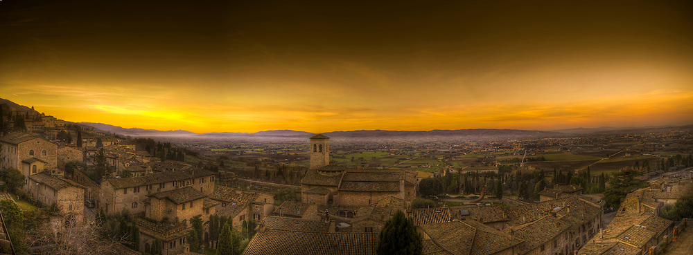 Dawn breaks across the valley below the ancient walled city of Assisi, Italy on a December morning and mist lays upon the valley floor.