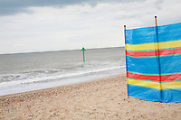 Windbreak pegged to shingle with tide marker at sea