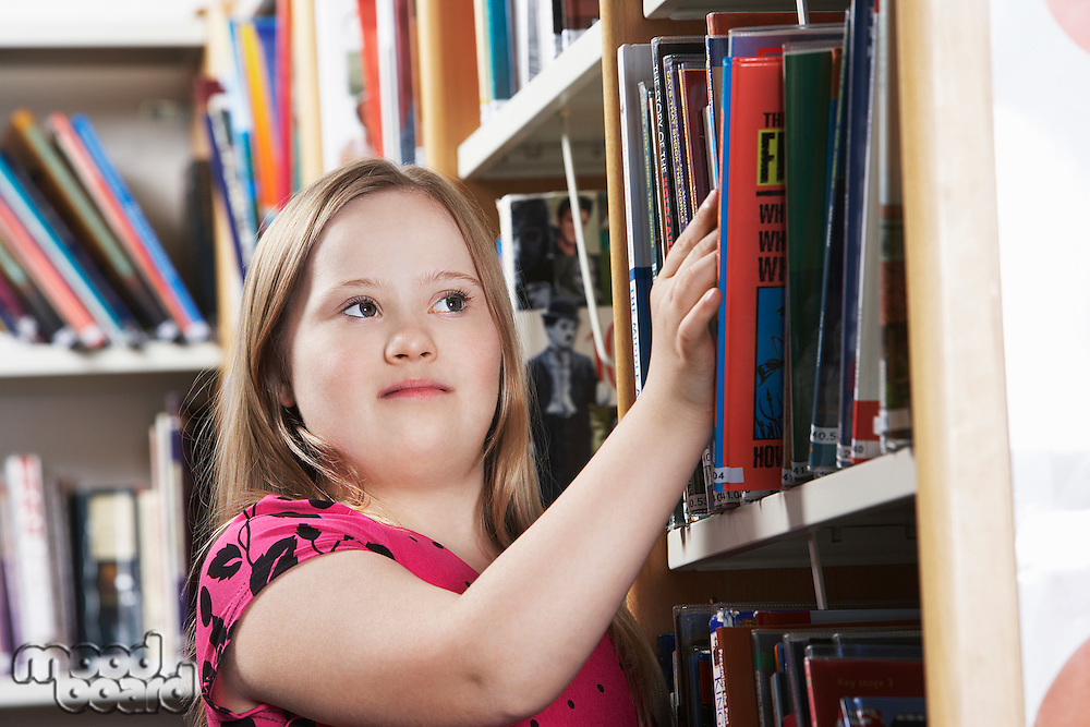 Girl (10-12) with Down syndrome taking book from shelf
