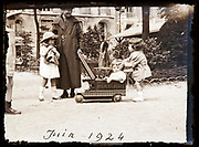 little children playing with grandmother in a park France 1924