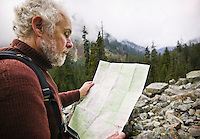 A mature man out in the wilderness usinga map to find his way. Washington Cascades, USA.