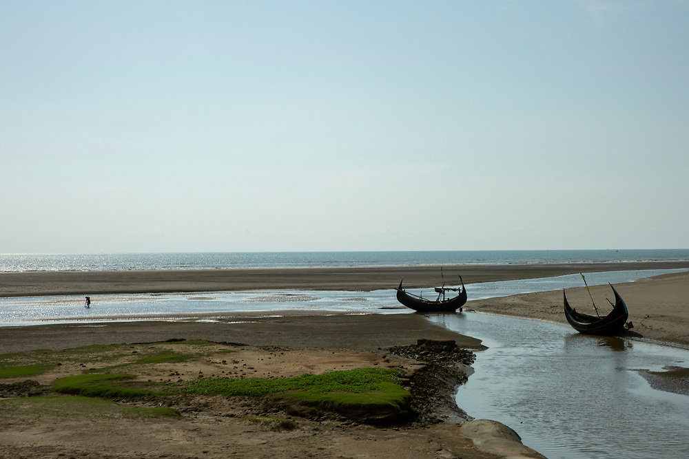 Two traditional Sampan fishing boats moor during low tide in an estuary that leads into the Bay of Bengal sea, near Sonar Para Bazar, Chittagong Division, Bangladesh, Asia.  In the distance, a fisherman fishes in the water. (photo by Andrew Aitchison / In pictures via Getty Images)