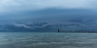 A wildly twisted roll cloud pushes its way towards shore ahead of a line of strong thunderstorms---in South Haven Michigan
