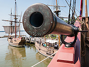 "Explore ship replicas Godspeed, Discovery, and flagship Susan Constant at Jamestown Settlement, in Virginia, USA. The mouth of a cannon defends the Susan Constant. The English Virginia Company sailed these three vessels 1606-1607 to found Jamestown, the first permanent English colony in the Americas. Jamestown Settlement, operated by the state's Jamestown-Yorktown Foundation, chronicles 1600s Virginia and the convergence of Powhatan Indian, European, and west central African cultures. Created as part of the 350th anniversary celebration in 1957 as Jamestown Festival Park, Jamestown Settlement is adjacent to the complementary ""Historic Jamestowne"" museum (which is on Jamestown Island, is the actual historic and archaeological site where the first settlers lived, and is run by the National Park Service and Preservation Virginia). (This composite photo is stitched from two overlapping images to improve depth of focus.)"