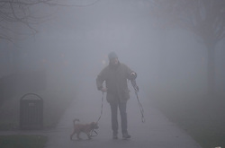 © Licensed to London News Pictures. 22/12/2016. London, UK. A man walks his dog through thick fog in in Dean Gardens, Ealing, West London on a cold winter morning. Temperatures over the upcoming Christmas period are expected to be unusually warm. Photo credit: Ben Cawthra/LNP