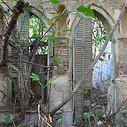 An abandoned building in a state of dereliction with garden plants invading the structure through arched windows with broken shutters, in the old town or Casc Antic of Tortosa, Tarragona, Spain. Tortosa is an ancient town situated on the Ebro Delta which has a rich heritage dating from Roman times. In recent years, many buildings in the old town have been abandoned and fallen into disrepair. Picture by Manuel Cohen