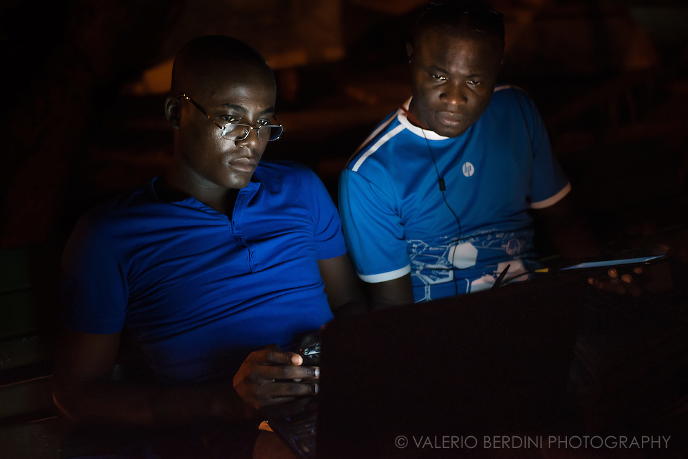 Two men in blue, lit up by the bluish light of their devices' screen, sit in Parque Fe del Valle in Havana, Cuba, on the evening of 29 December 2015. Cubans are highly educated people but have close to zero internet skills. During these early days of online accessibility they spend time learning how to explore and use the web. These people were aware of the photographer, but they continued their activity. This photo was not staged.<br /> <br /> This photo was published on the Guardian on 1 Feb 2016 http://www.theguardian.com/cities/gallery/2016/feb/01/havana-wi-fi-hotspots-revolution-street-life-in-pictures