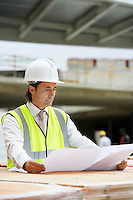 Construction worker examining building plans on site