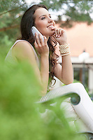 Side view of smiling young woman using mobile phone in park