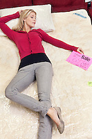 Young woman lying on new mattress in furniture store