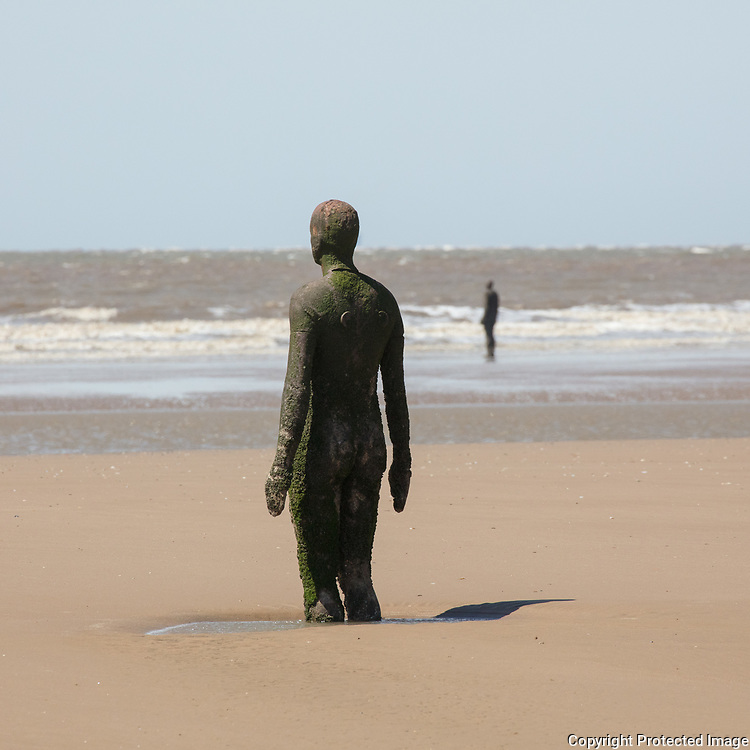 Two of the 100 figures which make up Another Place. Crosby Beach, Merseyside.