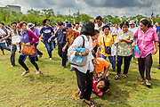 13 MAY 2013 - BANGKOK, THAILAND:    A child trips and is dragged by her mother as people rush onto Sanam Luang to collect blessed rice seeds after the Royal Ploughing Ceremony. After the ceremony, thousands of Thais, mostly family formers, rush onto the ploughed ground to gather up the blessed rice seeds sown by the Brahmin priests. The Royal Plowing Ceremony is held Thailand to mark the traditional beginning of the rice-growing season. The date is usually in May, but is determined by court astrologers and varies year to year. During the ceremony, two sacred oxen are hitched to a wooden plough and plough a small field on Sanam Luang (across from the Grand Palace), while rice seed is sown by court Brahmins. After the ploughing, the oxen are offered plates of food, including rice, corn, green beans, sesame, fresh-cut grass, water and rice whisky. Depending on what the oxen eat, court astrologers and Brahmins make a prediction on whether the coming growing season will be bountiful or not. The ceremony is rooted in Brahman belief, and is held to ensure a good harvest. A similar ceremony is held in Cambodia. PHOTO BY JACK KURTZ