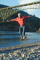 Senior man clicking heels in midair on beach Deception Pass Bridge Whidbey Island Washington USA.