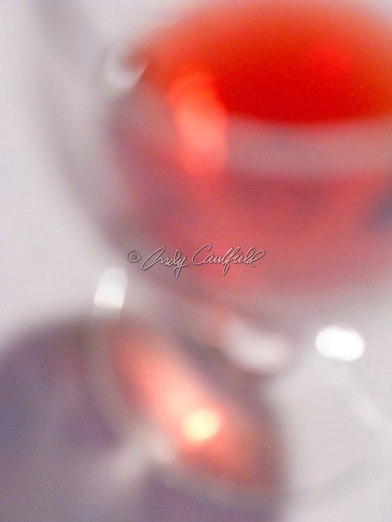 Red wine in wine glass on white table cloth.