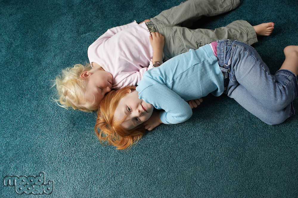 Sisters (3-6) lying on carpet one looking at camera view from above