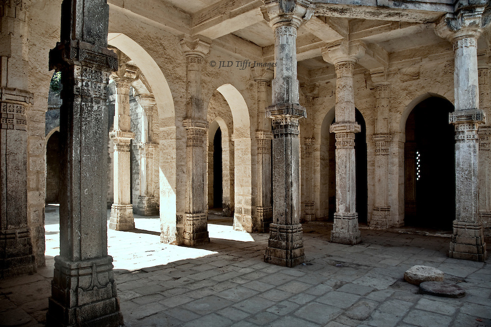 Palace and mosque at Uparkot, Junagadh, interior of colonnaded hall.  Sunlight streams in at one side, the other side shadowed.