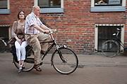 Een man fietst met een vrouw achter op de fiets door Groningen.<br /> <br /> A man is cycling with a woman at the backseat in Groningen.
