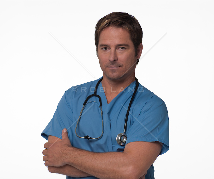 Doctor with his arms crossed standing in front of a white background