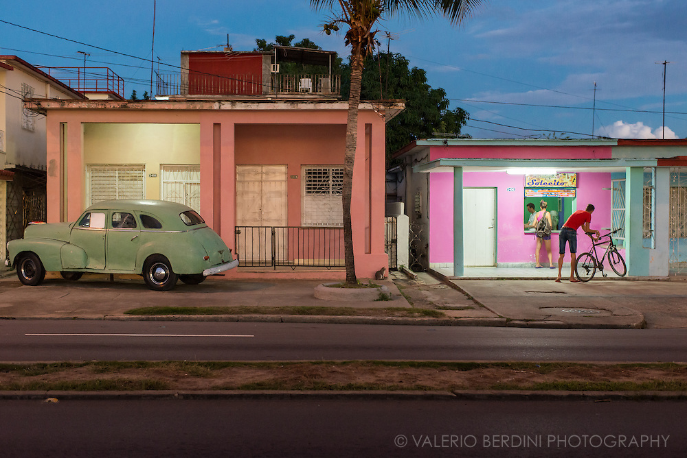 Pastel colours for an ice-cream place and a vintage American car in Cienfuegos after sunset. Cuba. 2015<br /> <br /> This photo has been published on a Gallery on the Independent http://www.independent.co.uk/news/world/americas/obama-in-cuba-what-the-country-will-likely-begin-to-lose-and-gain-after-the-president-s-historic-a6944246.html#gallery