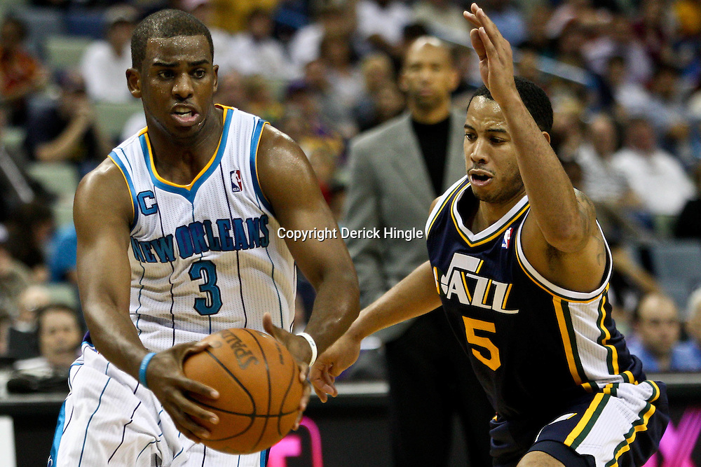 April 11, 2011; New Orleans, LA, USA; New Orleans Hornets point guard Chris Paul (3) drives past Utah Jazz point guard Devin Harris (5) during a game at the New Orleans Arena. The Jazz defeated the Hornets 90-78.  Mandatory Credit: Derick E. Hingle