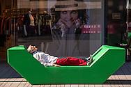 Europa, Deutschland, Duesseldorf, Mann liegt am Koe-Bogen auf einer Betonliege.<br /> <br /> Europe, Germany, Duesseldorf, man lying on a concrete sun lounger near the building Koe-Bogen.