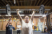 Stephen Reiners of San Jose performs a squat clean and press during a CrossFit program at ThirdSpace Fitness in San Jose, California, on July 6, 2015. (Stan Olszewski/SOSKIphoto for Content Magazine)