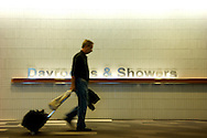 A traveller walks past a sign for dayrooms and showers in Narita Airport, Japan.