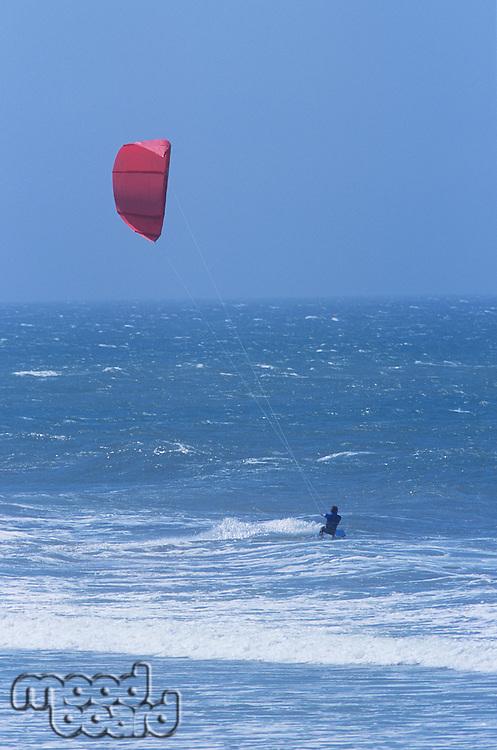 Person kitesurfing in sea