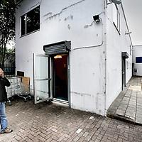 Nederland, Amsterdam , 24 september 2013.<br /> De laatste paar Asielzoekers moesten hun tijdelijk onderkomen vanmorgen in een gebouwtje aan de Nachtwachtlaan in het zg Vluchtpark verlaten.<br /> Inmiddels hebben ze weer een ander tijdelijk onbekend adres gevonden.<br /> Op de foto: 1 van de laatste asielzoekers uit het gebouwtje wrijft buiten de slaap uit de ogen nadat hij binnen door agenten is wakker gemaakt.<br /> Foto:Jean-Pierre Jans