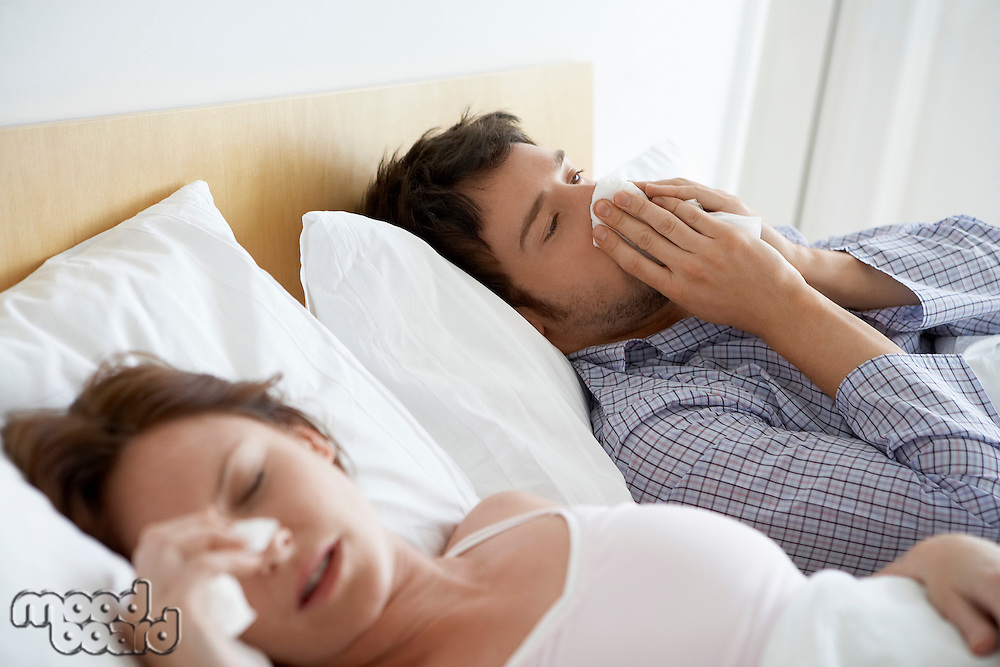 Couple with Colds Lying in Bed