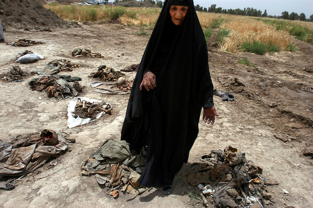 A woman seeks missing family at a mass grave thought to contain 10 to 15 thousand victims of Saddam Hussein's regime. The site was uncovered 20 kms north of the town of Hilla.  .Mahwheel, Iraq. 15 May 2003..Photo © J.B. Russell