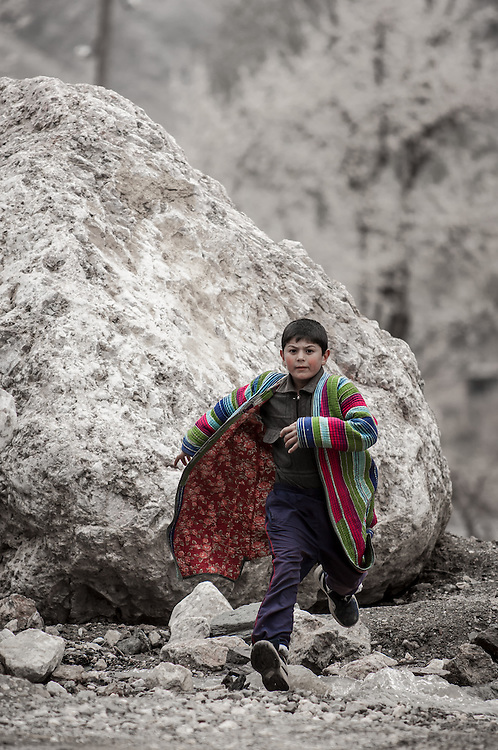 Portrait of a Tajik boy in a colourful coat jumping over rocks