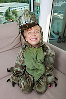 High angle portrait of happy boy in dinosaur costume sitting on sofa at home