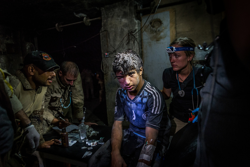 An Iraqi teenager receives treatment for a severely infected head wound at a trauma stabilization point on the edge of Mosul's old city after escaping the fighting. Volunteer medics from Global Response Management and Academy of Emergency Medicine, together with Iraqi forces, are providing emergency medical care around the clock, treating civilians and soldiers as the fighting continues.