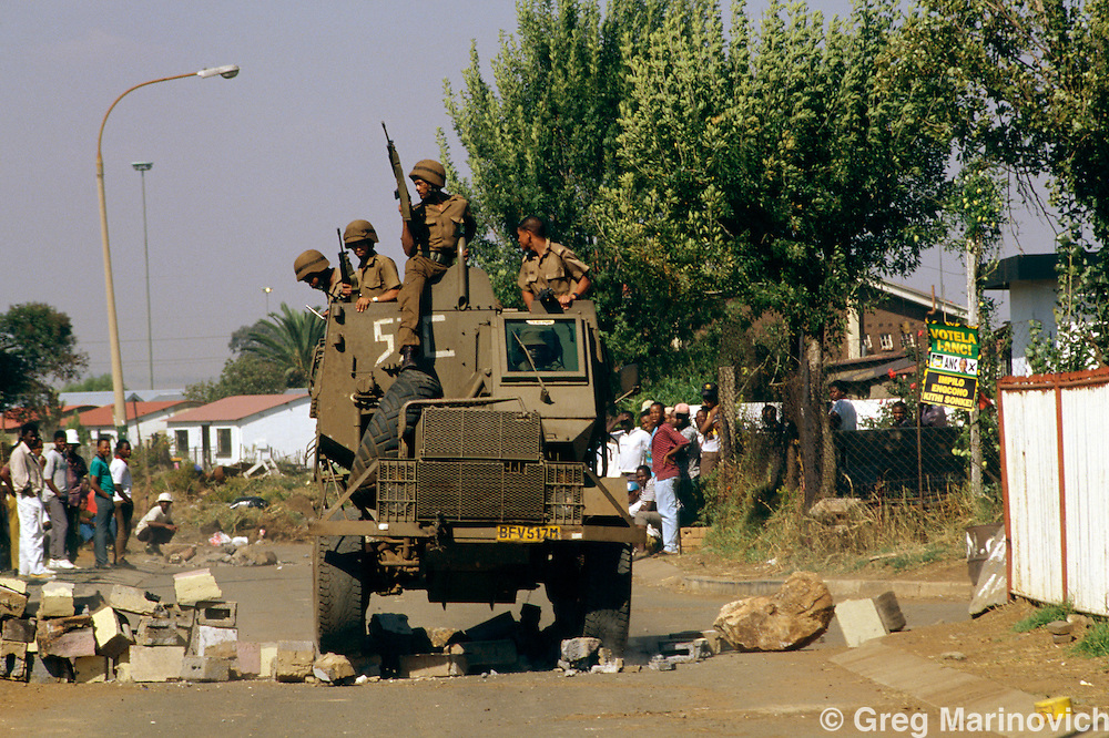 Thokoza, Transvaal, South Africa, 1990: A military armoured vehicle drives over barricades in Thokoza, on the East Rand.   South Africa 1994