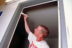 Young man painting door frame,