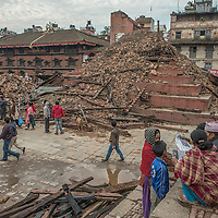 Family members read latest quake reports in newspaper close to a collapse temple in Kathmandu, Nepal 27 april 2015 following the devastating 7.9 magnitude earthquake that hit the country 25 April 2015.