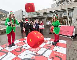 "Campaigners from Shelter Scotland raise awareness of their campaign ""Homelessness - Far From Fixed"" outside the Scottish Parliament in Edinburgh. They are joined by carol singers from Corstorphine Primary School, a Christmas tree and a giant snakes and ladders board game - Chance Not Choice - which illustrates how life chances affect people's ability to keep a roof over their head.<br /> <br /> Pictured: Izzy Gaughan and Amanda Donaldson from Shelter Scotland"