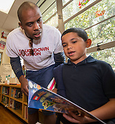 Ellis Wyms checks out a book with a student during a Touchdown Houston Read On literacy program at Ross Elementary School, December 2, 2016.