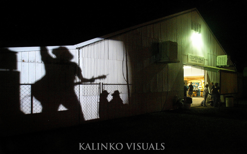 People walk by a shadow of Phillip Sweet of the Little Big Town band at the Umatilla County Fair as a spotlight from the main stage casts it on the side of a barn Tuesday Aug. 11, 2006, in Umatilla, Ore. ..Published: Aug 11, 2006