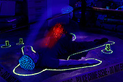 A ghost rises from the body of a dead man outlined with glowing chalk. Blacklight Photography.