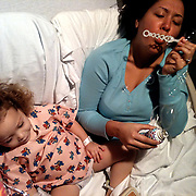 Leilani Frizzelle blows bubbles with her daughter Holly Larue, 2 in Larue's room in December 2012. On December 27, 2012 two year old Holly Larue Frizzelle was diagnosed with Acute Lymphoblastic Leukemia. What began as a stomach ache and visit to her regular pediatrician led to a hospital admission, transport to the University of North Carolina Children's Hospital, and more than two years of treatment.