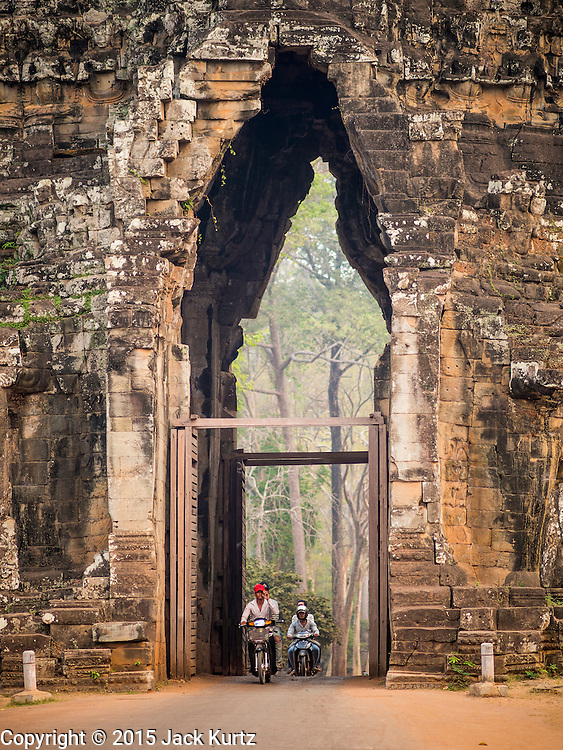 """14 MARCH 2105 - SIEM REAP, SIEM REAP, CAMBODIA:  Motorcyles pass through the west gate of Angkor Thom. The area known as """"Angkor Wat"""" is a sprawling collection of archeological ruins and temples. The area was developed by ancient Khmer (Cambodian) Kings starting as early as 1150 CE and renovated and expanded around 1180CE by Jayavarman VII. Angkor Wat is now considered the seventh wonder of the world and is Cambodia's most important tourist attraction.  PHOTO BY JACK KURTZ"""