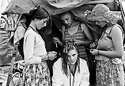 Young white female gets hair plaited by three other young females in front of a small tent at glastonbury festival. Glastonbury 1992