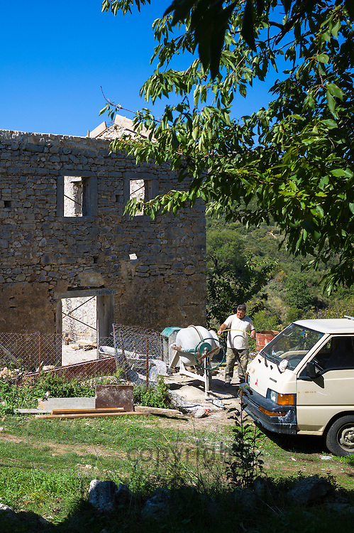 Builder working at cement mixer for masonry restoring derelict house in ruins in re-development in village, Old Perithia - Palea Perithea, Corfu, Greece
