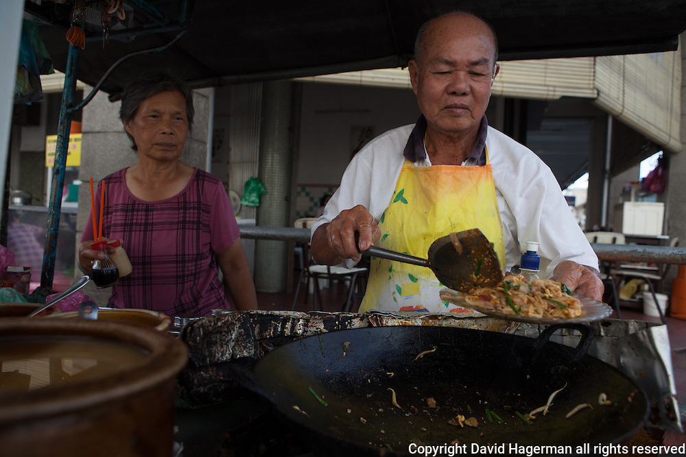 serving char koey teow, rice noodles fried with shrimp and bean sprouts, george town,penang, malaysia