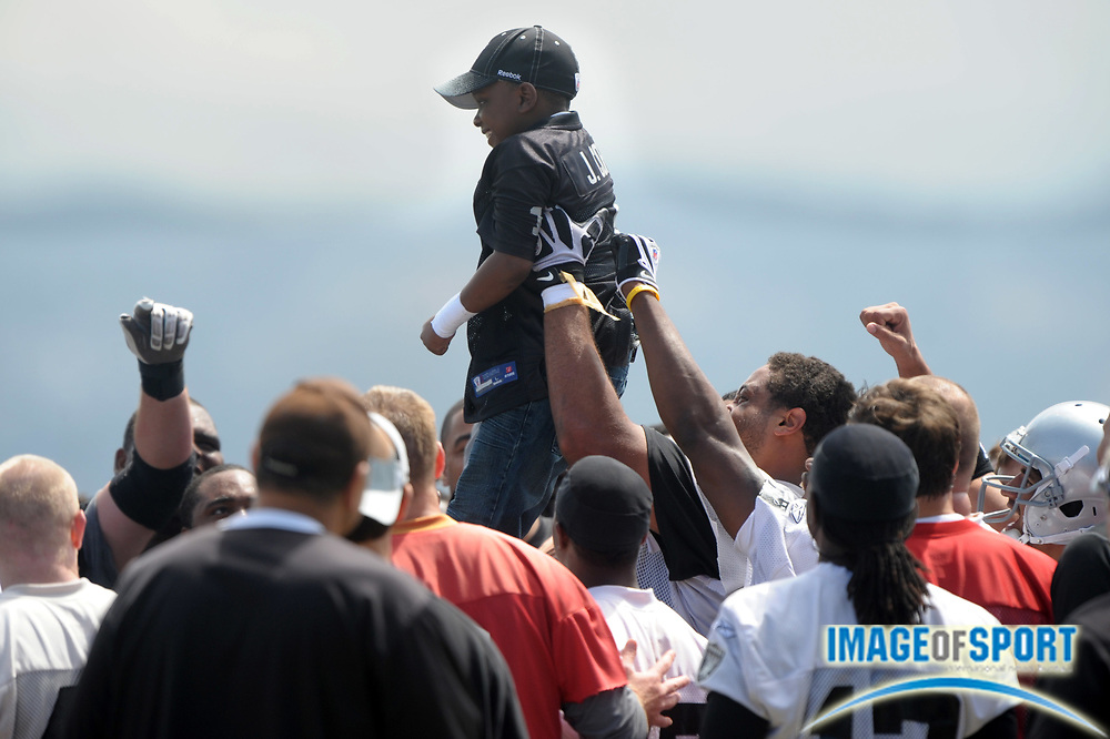 May 26, 2010; Alameda, CA, USA; Oakland Raiders tackle Langston Walker (70) hoists Make-A-Wish Foundation child Jailen Cooper during a team huddle at organized team activities at the Oakland Raiders practice facility.