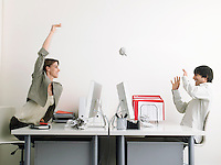 Woman throwing paper at man in office side view