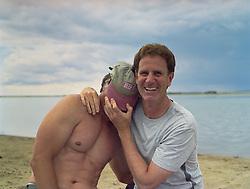 Two men at a lake playing around