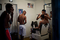 Mateus, 22, who opened a barber shop three weeks ago in his home, shaves his friend's head, Bruno, 16, right, in Complexo do Caju, Rio de Janeiro, Brazil, on Friday May 10, 2013. <br /> <br /> In the early hours of Sunday, March 3, 2013, about 1,400 Brazilian security forces occupied 13 communities during a joint public security operation to install a Pacifying Police Unit (UPP) in two Rio de Janeiro favelas, Complexo do Caju and Barreira do Vasco. Elite police units backed by armored military vehicles and helicopters invaded the neighborhood in an on-going policing program aimed to drive violent and heavily armed drug gangs out of Rio's poor communities, where the traffickers have ruled for decades. For the community of Caju, that is ADA (Amigos de Amigos) and CV (Comando Vermelho).